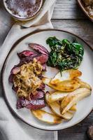 Filete con patatas al horno y ensalada verde sobre fondo de madera foto