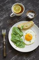 huevo frito y espinacas frescas en un plato blanco