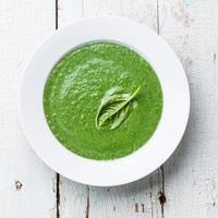 Green spinach soup in a white bowl