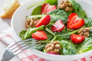 Salad with baby spinach, strawberry, nuts, oil, bread, plaid napkin
