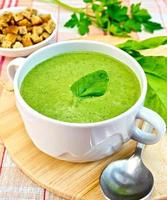 Soup puree with spinach leaves and spoon on fabric photo