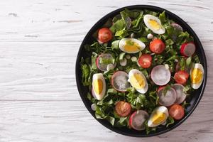 Fresh spring salad with eggs on table. horizontal top view photo