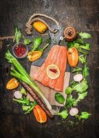 Salmon fillets on cutting board with vegetables and spices ingredients