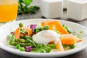 Ensalada de verano con huevo escalfado. foto