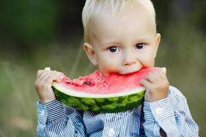 little boy eats watermelon
