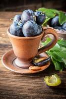 Fresh juicy plums with leaves in a ceramic pot on photo