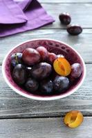 Fresh plums in a small bowl photo