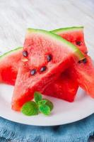 sliced watermelon with mint leaf on a white plate