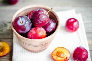Fresh pink plum in pottery on gray wooden table, rustic photo