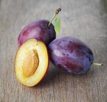 ripe plums on old wood table