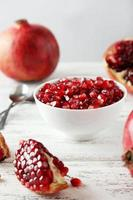 Delicious pomegranate fruit in bowl on white wooden background