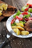 Grilled meat with salad and roasted potatoes.