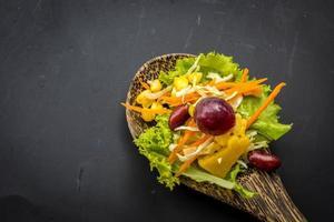 Ensalada de maíz en la cuchara de mesa negro en el piso. foto