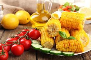 mazorcas de maíz a la parrilla en la mesa, primer plano foto