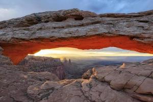 View of sunrise through an arch Mesa.