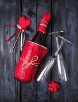 bottle of champagne in red paper, heart on blue background photo