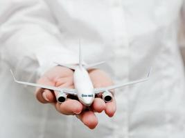 Business person holding airplane model. Transport, aircraft industry, airline photo