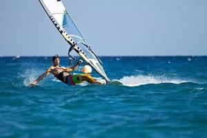 jonge man surfen op de wind in spatten van water