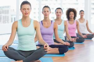 Las mujeres deportivas en meditación posan con los ojos cerrados foto