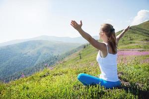 jovem mulher meditar no topo da montanha