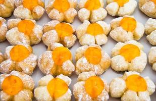 Row of fancy bread with orange jelly surface photo