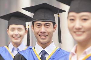 três graduados da universidade sorrindo em uma fileira