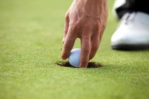 Person holding golf ball, close-up