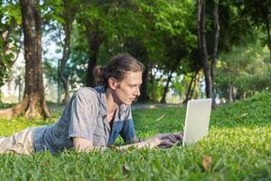 Yang business man is working outdoors with laptop computer