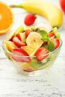 Fresh fruit salad in bowl on white wooden background
