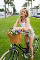 Young charming female cyclist posing with her vintage bike outdoors photo