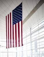 American flag in front of glass windows
