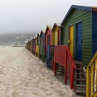 Brightly painted beach cabanas on a foggy morning at Muizenberg
