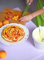 Woman hand cut peach for cake photo