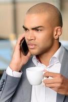 Pleasant businessman drinking coffee photo