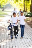 niños caminando con una bicicleta con padres detrás