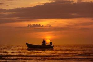 Silhouette fishing boat at sea sunset background.