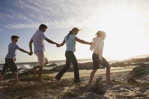 família caminhando na praia