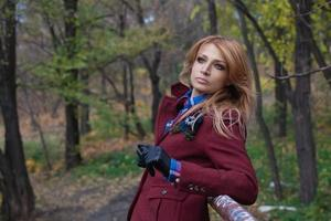 Beautiful blonde woman in jacket and leather gloves in autumn forest