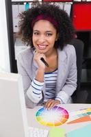 sonriente mujer editor de fotos en el escritorio de la oficina
