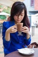 Executive Chinese Woman Drinking chocolate in outdoor cafe