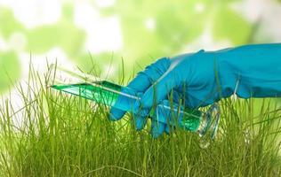 mano con frasco y hierba foto