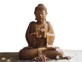 Buda de madera en meditación aislado en fondo blanco. foto