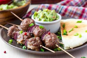 kebab de carne, bolas de carne en brocheta con cebolla, salsa de guacamole foto