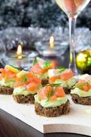 Appetizer canapes of bread with avocado, red fish salmon, lemon
