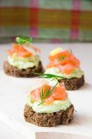 Delicious appetizer canapes of black bread, avocado and red fish
