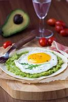 Breakfast with fried egg and sauce of avocado on grilled