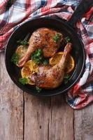 Fried duck leg with oranges in pan vertical top view