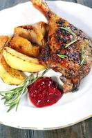 Duck leg with potatoes and cowberry sauce.