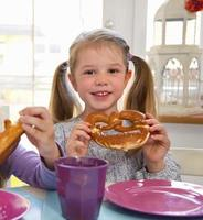 Girls eating pretzels at table photo
