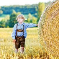Adorable little kid boy having fun with hay stack